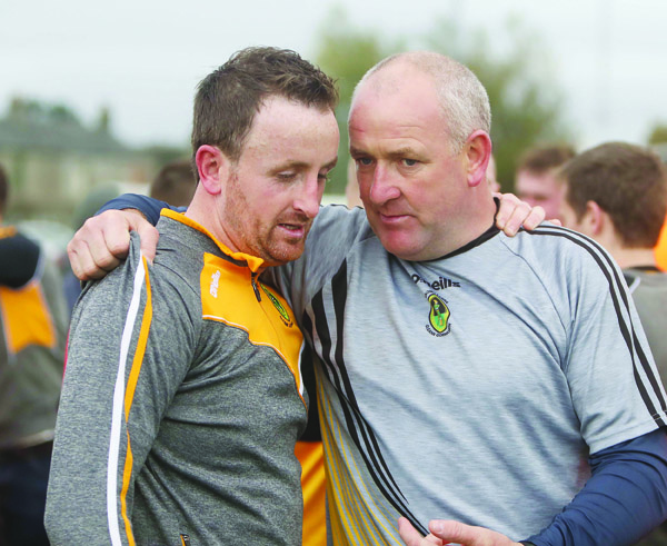 Naomh Éanna midfielder Philly Curran and manager Frank Fitzsimons embrace following the county final win over Gort na Móna