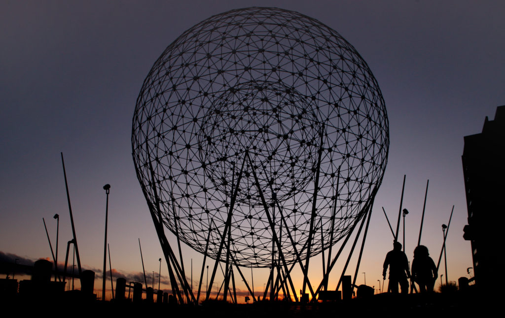 Dusk falls as a couple make their way past the Rise sculpture at Broadway roundabout