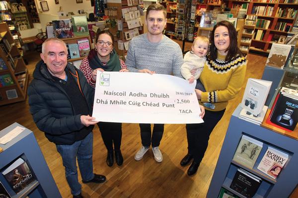 Paid Ó Cianáin from Taca presents a cheque for £2,500 to Eibhlin Bhreathnach, Ryan Carlin, Odhran Nic Giolla Fhinnein and Mairead Nic Giolla Fhinnein from Naíscoil Aodha Dhuibh