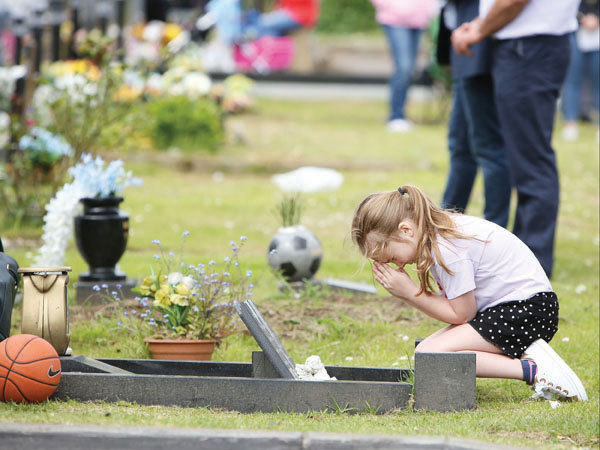 Erin Shannon prays at the family grave during Cemetery Sunday at Milltown