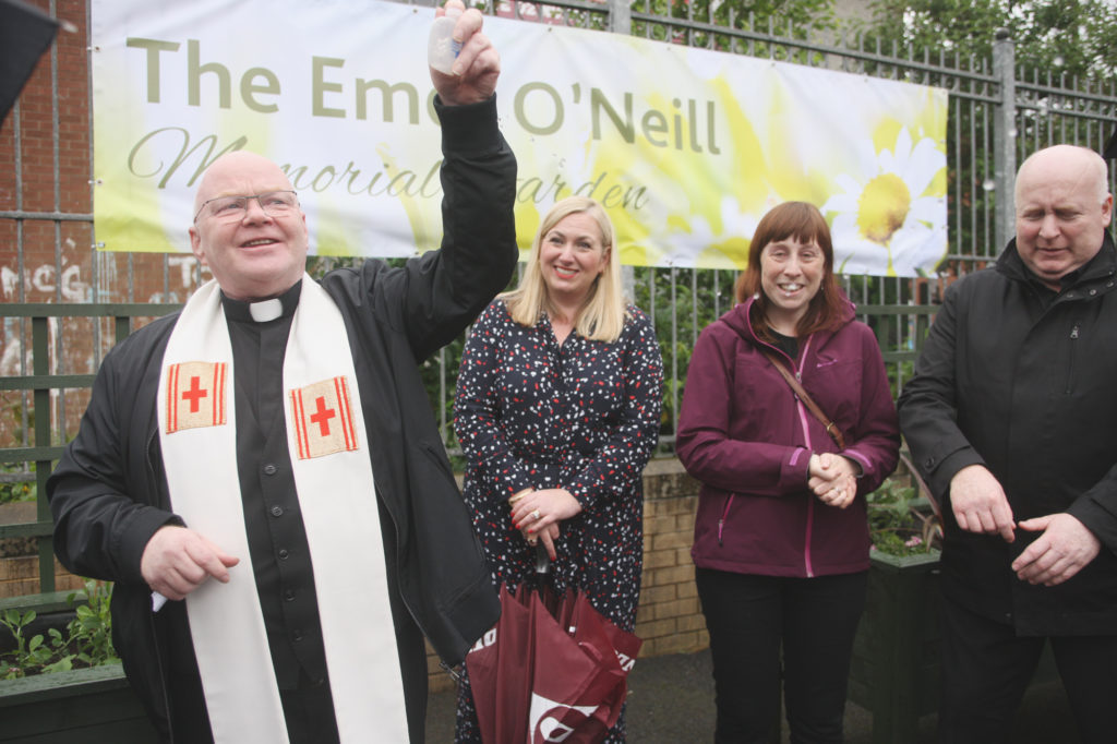 IN MEMORY: Fr Devlin blesses the new memorial garden in St Clare's Primary School, which is dedicated to the school's late caretaker Emer O'Neill