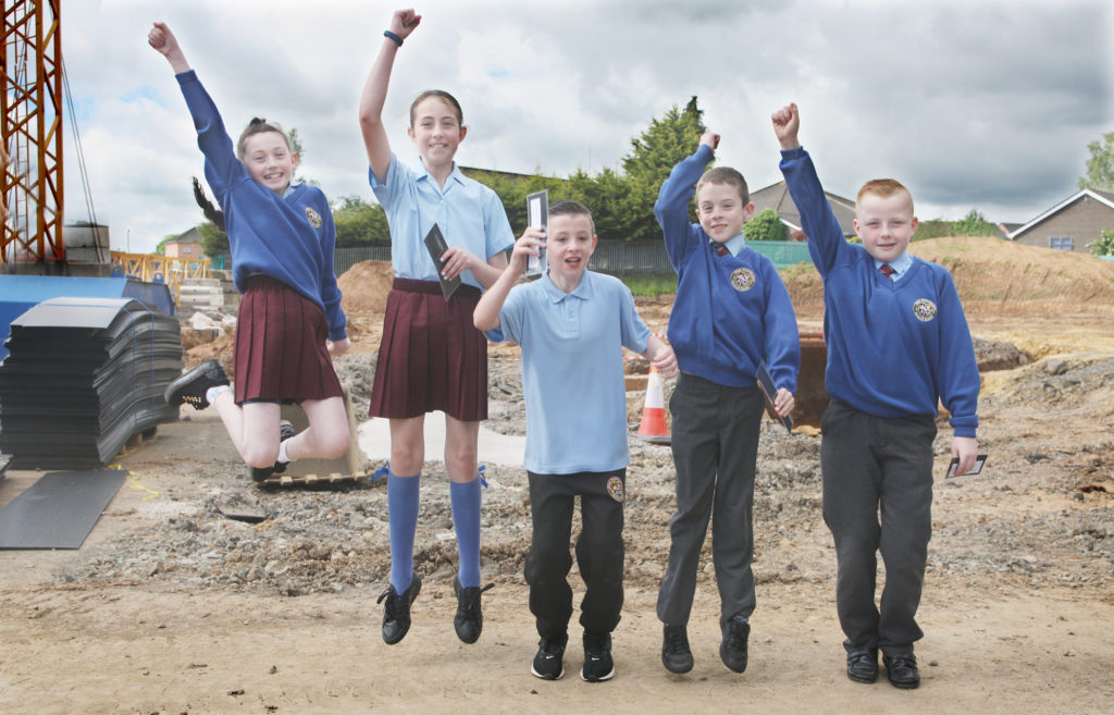 Holy Evangelists Primary School pupils Aoife, Holly Rose, Liam, Nathan and Aodh‡n jump with joy as Bishop Noel Treanor blesses the foundations of the new school building in Twinbrook