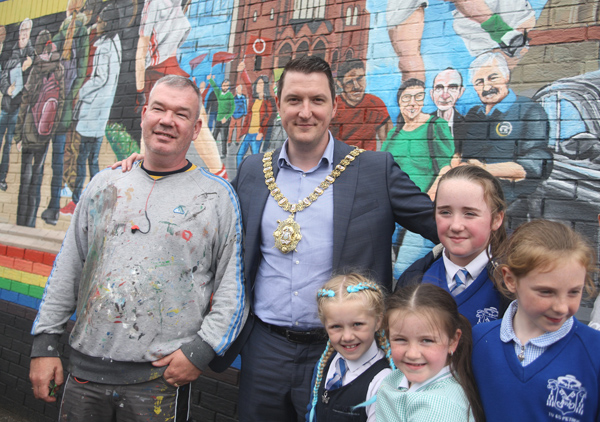 John Finucane unveiling a new mural celebrating West Belfast with artist Michael Doherty and local children on the lower Falls