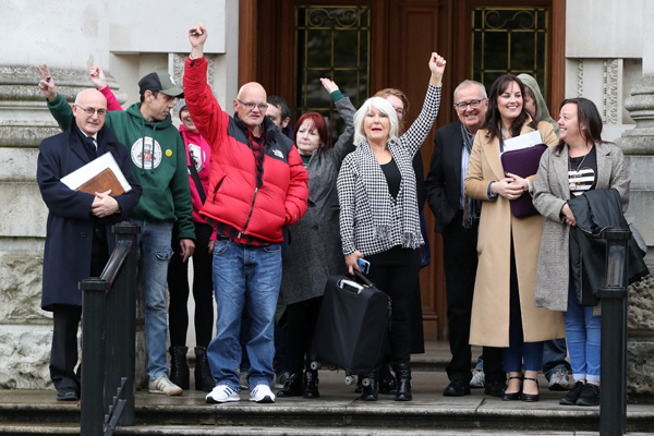 Margaret McGuckin SAVIA (Survivors and Victims of Institutional Abuse) and survivors raise their hands in victory outside the High Court In Belfast